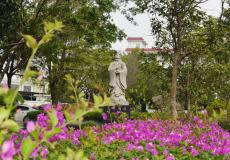 绿树掩映鲜花映衬的孔子雕像